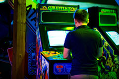 PRAGUE - CZECH REPUBLIC, August 5, 2017 - Young man playing an old vintage arcade game. In a room room full of of 90s Era Old Arcade Video Games Royalty Free Stock Image