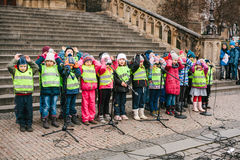 Prague, Czech Republic, December 15, 2016: The choir of children sing Christmas songs on the square next to the temple. People are watching the performance Stock Image
