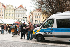 Prague, Czech Republic - December 25, 2016: Czech policemen on a Christmas day help the tourist - show the desired place. Of attractions on the map. Respectful Royalty Free Stock Photo
