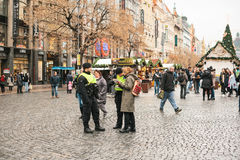Prague, Czech Republic - December 25, 2016: Czech policemen on a Christmas day help the tourist - show the desired place. Of attractions on the map. Respectful Royalty Free Stock Images