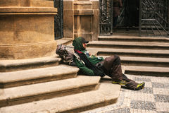 Prague, Czech Republic December 24, 2016 - Homeless hungry poor man sitting on the sidewalk in the city center. Unhappy. Man stock photography