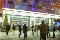 People coming in and out from the large decorated shopping center Palladium in Prague on the Republic square. PRAGUE, CZECH REPUBLIC - DECEMBER, 13, 2017 Royalty Free Stock Photos