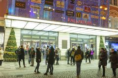 People coming in and out from the large decorated shopping center Palladium in Prague on the Republic square. PRAGUE, CZECH REPUBLIC - DECEMBER, 13, 2017 Royalty Free Stock Images