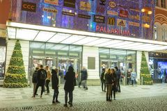 People coming in and out from the large decorated shopping center Palladium in Prague on the Republic square. PRAGUE, CZECH REPUBLIC - DECEMBER, 13, 2017 Stock Photos