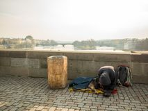 PRAGUE, CZECH REPUBLIC - FEBRUARY 20, 2018: Kneeling man and his dog begging on the Charles Bridge.Destination for traveler around royalty free stock photography
