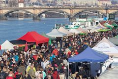 People shopping at the popular farmers market at the Naplavka riverbank in Prague. PRAGUE, CZECH REPUBLIC - FEBRUARY 16, 2019: People shopping at the popular stock photos