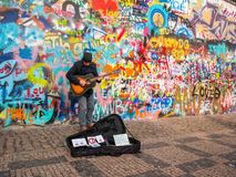 PRAGUE, CZECH REPUBLIC - FEBUARY 20, 2018: Street Busker performing Beatles songs in front of John Lennon Wall on Kampa Island.Old stock photo