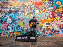 PRAGUE, CZECH REPUBLIC - FEBUARY 20, 2018: Street Busker performing Beatles songs in front of John Lennon Wall on Kampa Island.Old. Town near Charles Bridge.The Stock Photo