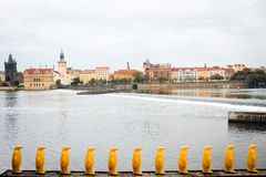 Prague, Czech Republic - figures of yellow penguins on the embankment of the Vltava River overlooking the old city stock image