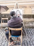 Caricaturist drawing female portrait. PRAGUE, CZECH REPUBLIC - MARCH 8 2017: Prague caricaturist drawing female portrait on Charles Bridge Stock Photos