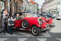 Tourists talk with driver of red oldtimer car. Prague, Czech Republic - May 2, 2017: Tourists talk with driver of red oldtimer car on the street of old Prague Stock Photo