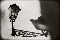 Prague, Czech Republic: Not a lighted lantern on the wall. From him on the wall pronounced shadow and outlines. Royalty Free Stock Images