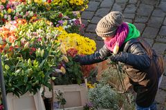 Woman buys flowers at the popular farmers market at the Naplavka riverbank in Prague. PRAGUE, CZECH REPUBLIC - NOVEMBER 17, 2018: Woman buys flowers at the royalty free stock photography