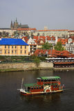 PRAGUE, CZECH REPUBLIC. Old-fashioned boat floating on the Vltava river along the Mala Strana bank and Prague Cas Royalty Free Stock Photos