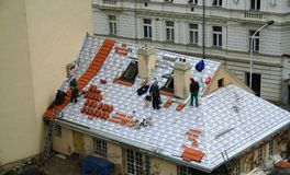 Prague, Czech Republic. Red roofs of Prague. Workers on top of the roof repairing slates stock photography