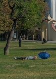 Prague, Czech Republic - September 10, 2019: bold Man sleeps on the grass in a sunny day at kampa park royalty free stock photography
