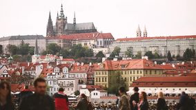 Prague, Czech Republic. Tourists People Walking In City With Prague Castle And Metropolitan Cathedral Of St Vitus. Wenceslaus And Adalbert On Background stock footage