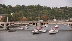Prague, Czech Republic. View Of The Manes Bridge And Vltava River In Autumn Day. Tour Boats And Sightseeing Ships. Floating Under Bridge In Vltava River stock footage