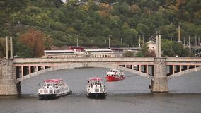 Prague, Czech Republic. View Of The Manes Bridge And Vltava River In Autumn Day. Tour Boats And Sightseeing Ships. Floating Under Bridge In Vltava River stock video footage
