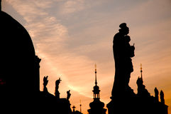 Prague Dawn. Statues on rooftops in Prague, near Charles bridge, silhouetted against sunrise sky Royalty Free Stock Images