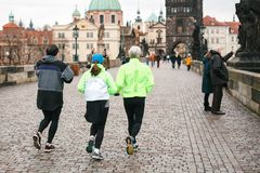 Prague, December 24, 2016: Athletes have a morning run in the winter on the Charles Bridge in Prague in the Czech Royalty Free Stock Images