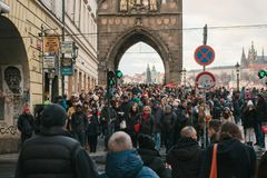 Prague, December 24, 2016: A crowd of locals and tourists cross the road to the green light next to the Charles Bridge Stock Images