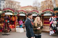 Prague December 15, 2016: Den europeiska parmannen och kvinnan i julen marknadsför den varma funderade vin och klockan för drink arkivfoto