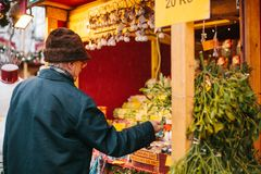 Prague, December 15, 2016: An elderly man buys Christmas presents to his grandchildren at the Christmas market. Gifts. For the holiday. Celebrating Christmas royalty free stock photo