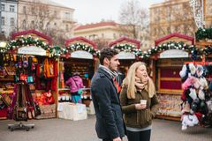 Prague, December 15, 2016: European couple man and woman in the Christmas market drink hot mulled wine and watch. Christmas performances. Celebrating Christmas stock photo