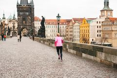 Prague, December 24, 2016: The girl athlete has a morning run in the winter on the Charles Bridge in Prague in the Czech Royalty Free Stock Photos