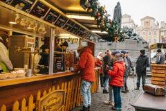 Prague December 13, 2016: Julmarknad i den huvudsakliga fyrkanten Mannen köper funderat vin Garneringar i Arkivfoto