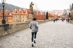 Prague, December 24, 2016: A man athlete has a morning run in the winter on the Charles Bridge in Prague in the Czech Stock Image