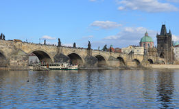 PRAGUE - FEB 23: Tourist boat sailing under the Charles Bridge Stock Photos