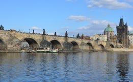 PRAGUE - FEB 23: Tourist boat sailing under the Charles Bridge Stock Photos