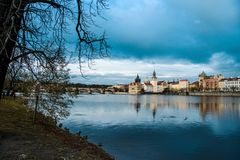 Prague and its reflection in the river. Prague cityscape seen from a little island on the Moldava river Stock Image
