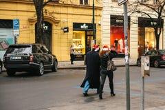 Prague, le 24 décembre 2016 : Noël à Prague Couples inconnus - homme et femme dans des chapeaux rouges de nouvelle année marchant Image libre de droits