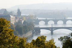 Prague in morning fog. This is a morning view of the bridges on the Vltava River in Prague, Czech Republic. Yellow trees flavor the cityscape Stock Photo