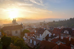 Prague in the Morning Sunshine. Prague as seen from the castle in the fog as the sun comes up over the red rooftops Royalty Free Stock Images