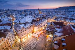 Prague Old Town in snow during late sunset with yellow lights and blue sky royalty free stock image