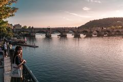 Prague, République Tchèque - 10 septembre 2019 : Jeune position asiatique de femme à côté de la rivière de Vltava pendant le couc photo stock