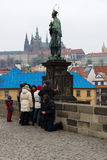 Prague. Sculpture of John of Nepomuk on Charles Bridge. Beggar near tourists. Stock Photos