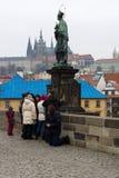 Prague. Sculpture of John of Nepomuk on Charles Bridge. Beggar near tourists. Stock Photos