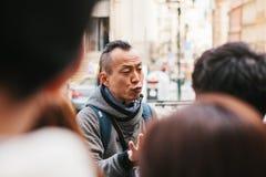 Prague September 21, 2017: Den asiatiska handboken berättar känslomässigt asiatiska turister om sikten av staden och intressera Arkivbilder