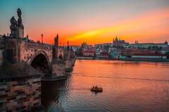 Prague slott och Charles bro på solnedgången, Tjeckien royaltyfri bild