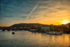 Prague solnedgång vid den Vltava floden med varmt ljus för fartyg royaltyfri foto