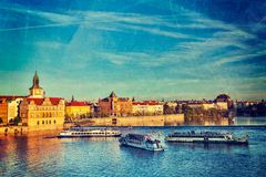 Prague Stare Mesto embankment view from Charles bridge. Vintage retro hipster style travel image of Vltava river with tourist boats and Prague Stare Mesto Stock Photos