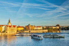 Prague Stare Mesto embankment view from Charles bridge. Vltava river with tourist boats and Prague Stare Mesto embankment view from Charles bridge on sunset Royalty Free Stock Photo