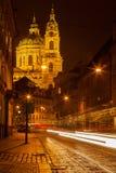 Prague street with Saint Nicolas church Stock Photos