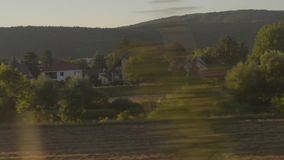Prague suburb countryside meadow field river trees sunset light seen from train stock video