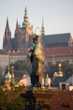 Prague sunrise scenery. Statue of St. John of Nepomuk on Charles bridge with Prague Castle on the background during sunrise Royalty Free Stock Image